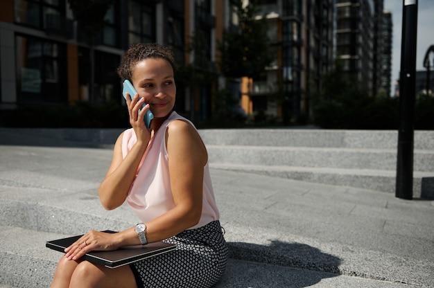 휴대 전화로 얘기하고, 멀리보고, 도시의 높은 건물 배경에서 카메라에 포즈를 취하는 아름다운 아프리카계 미국인 여성의 초상화. 비즈니스, 사무실, 프리랜서, 원격 작업, 온라인 개념