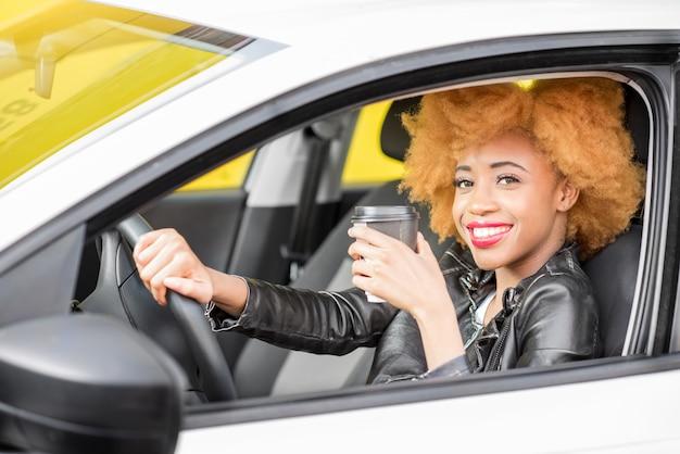 黄色の背景の車に座っているコーヒーカップと革のジャケットの美しいアフリカの女性の肖像画