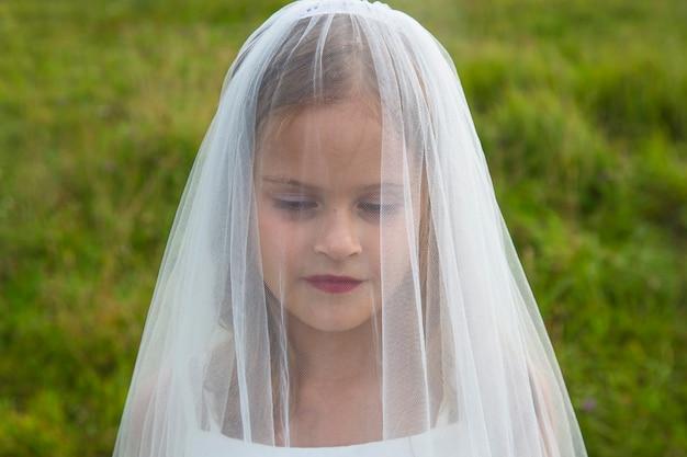 Портрет красивой и нежной девушки невесты в фате на фоне поля и травы в летний день