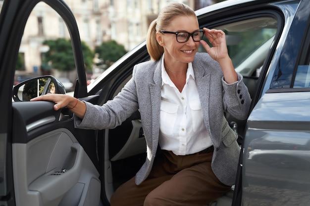 Портрет красивой и счастливой деловой женщины в очках, выходящей из своей современной машины