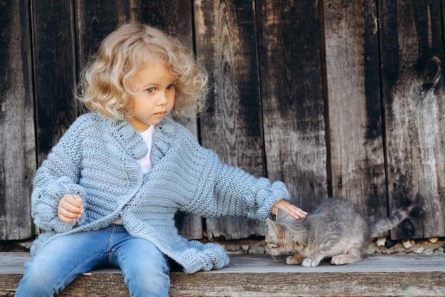 木製の壁の近くで子猫と遊ぶ青いニットのセーターで美しく幸せな巻き毛の少女の肖像画
