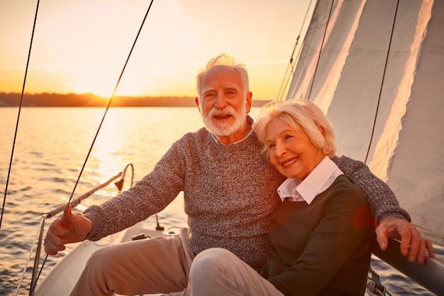 抱き締めて素晴らしい夕日を楽しんでいる間、愛の美しく幸せな年配のカップルの肖像画