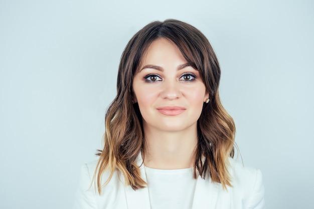 白い背景に笑みを浮かべて白い医療用ガウンの美しい若い女性のシックなメイクと髪型の肖像画