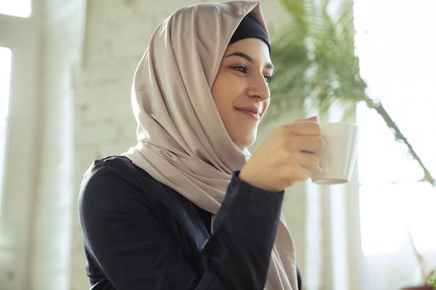 오픈스페이스나 사무실에서 일하는 동안 히잡을 쓴 아름다운 아라비아 여성 사업가의 초상화