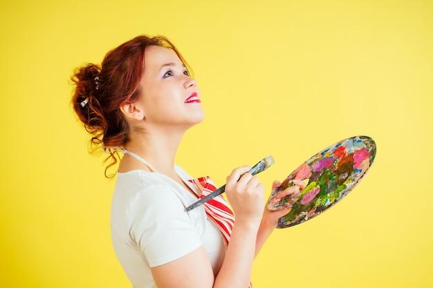 スタジオで黄色の背景にパレットとブラシを保持しているエプロンの美しいアーティストの肖像画。インスピレーションとミューズのアイデア。