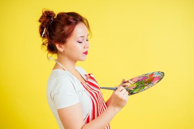 スタジオで黄色の背景にパレットとブラシを保持しているエプロンの美しいアーティストの肖像画