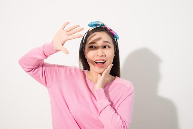 明るい太陽の光、幸せな夏の休暇の手で顔を覆う美しいアジアの女の子の肖像画
