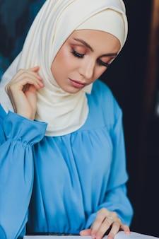 근접 촬영보기에서 배경으로 흰색 커튼에 포즈 흰 블라우스와 파란색 hijab를 입고 아름다운 아시아 이슬람 여자 모델의 초상화