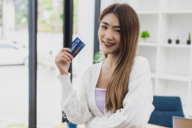 クレジットカードを持っている美しいアジアの女性の肖像画、クレジットカードで支払うオンラインショッピングの概念、若いアジアのビジネスウーマン、現代の女性エグゼクティブ、ビジネスリーダー。