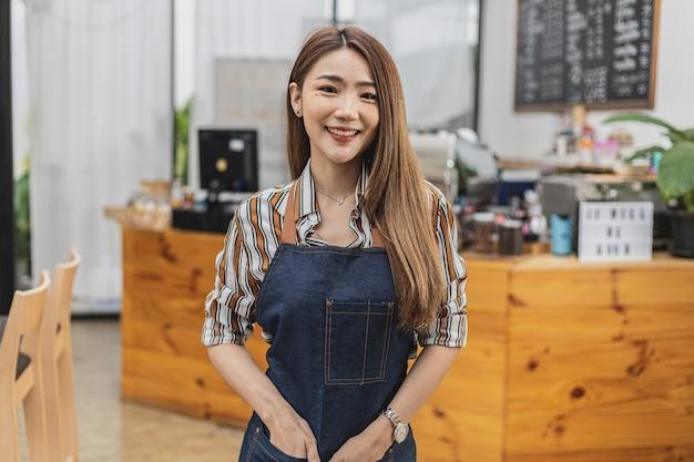コーヒーショップに立っているエプロンに身を包んだ美しいアジア人女性の肖像画である彼女は、飲食店のコンセプトであるコーヒーショップを経営しています。ビジネスウーマンによる店舗運営。