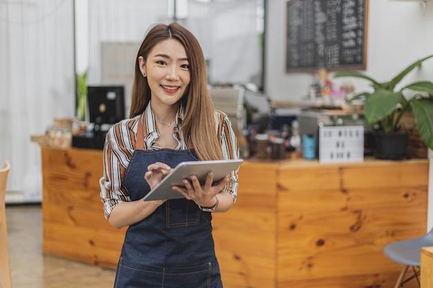 カフェでタブレットを使って立っているエプロンに身を包んだ美しいアジア人女性の肖像画。彼女は、飲食店のコンセプトであるコーヒーショップを経営しています。ビジネスウーマンによる店舗運営。