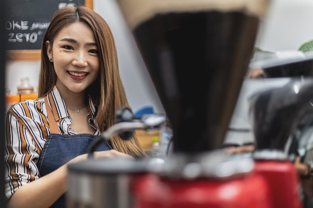 コーヒーマシンを使用してエプロンで美しいアジアの女性の肖像画、彼女はコーヒーショップ、飲食店のコンセプトを所有しています。ビジネスウーマンによる店舗運営。