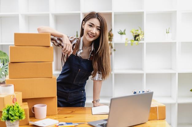 사무실에 있는 아름다운 아시아 여성의 초상화와 탁자 위에 있는 많은 소포 상자, 그녀는 개인 운송 회사를 통해 포장하고 배송합니다. 온라인 판매 및 온라인 쇼핑 개념입니다.