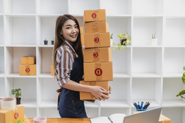 많은 소포를 들어 올리는 아름다운 아시아 여성의 초상화, 그녀는 온라인 상점을 소유하고 개인 운송 회사를 통해 포장하고 배송합니다. 온라인 판매 및 온라인 쇼핑 개념입니다.