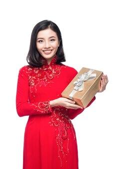 Портрет красивой азиатской женщины на традиционном фестивальном костюме ао дай с подарочной коробкой. тет-праздник. лунный новый год.