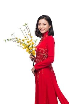 Портрет красивой азиатской женщины в традиционном фестивальном костюме ао дай с цветком дерева хоа май (ochna integerrima). тет-праздник. лунный новый год.