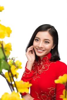 Hoa mai 나무(ochna integerrima) 꽃을 들고 있는 전통 축제 의상 ao dai를 입은 아름다운 아시아 여성의 초상화. 설 연휴. 구정.