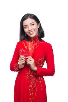 赤いポケットを持っている伝統的な祭りの衣装アオザイの美しいアジアの女性の肖像画-幸運なお金。テトホリデー。旧正月。