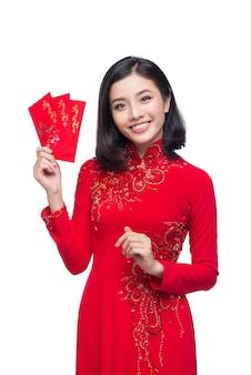 Портрет красивой азиатской женщины в традиционном фестивальном костюме ао дай, держащей красный карман - счастливые деньги. тет-праздник. лунный новый год.
