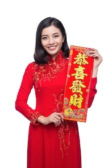 신년 두루마리 구정 휴일을 보여주는 전통 축제 의상 아오자이를 입은 아름다운 아시아 여성의 초상화. 구정. 텍스트는 행복과 부자가 되는 것을 의미합니다.