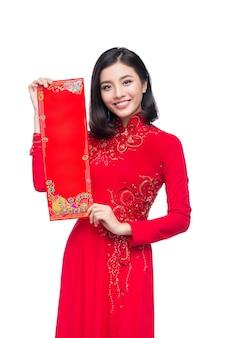 Портрет красивой азиатской женщины в традиционном фестивальном костюме ао дай показывает новогодние свитки тет праздник. лунный новый год.