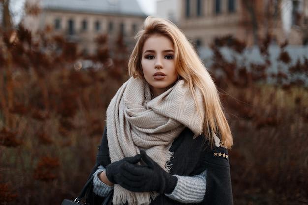 니트 스웨터에 검은 장갑에 베이지 색 빈티지 스카프와 세련된 검은 코트에 아름다운 매력적인 젊은 여자의 초상화