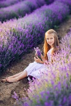 Портрет красивой девочки в поле лаванды. летнее фото в фиолетовых тонах.