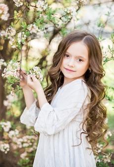 春に咲く庭で美しい女の赤ちゃんの肖像画。白い花を背景にした女の子。