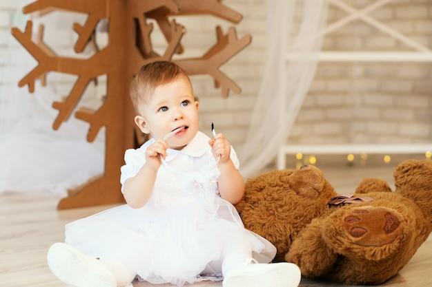 クリスマスの装飾が施されたインテリアに柔らかい茶色のテディベアを持つ美しい女の赤ちゃんの肖像画。