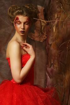 赤いドレスを着た美しい金髪の女性の肖像画。クリエイティブなメイクとヘアスタイル。ファンタジーハウスで撮影。