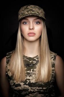 Портрет красивой белокурой женщины-солдата в военной форме на черном фоне