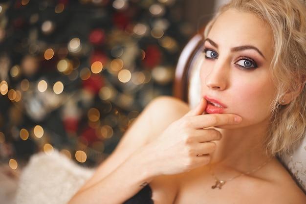 新年の花輪を背景に美しい金髪の肖像画。