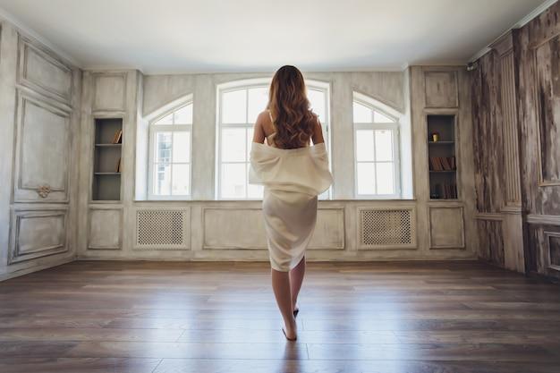 インテリアの美しい金髪の花嫁の肖像画。バスローブで朝の若い花嫁。結婚式の写真。笑顔でかわいい女の子が立っています。