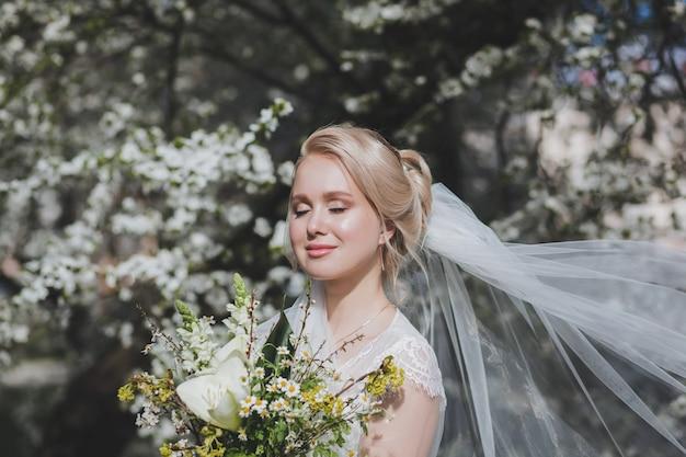 Портрет красивой блондинки невесты с цветами в цветущем весеннем парке