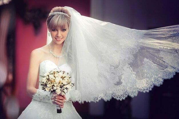 手にウェディングブーケを持つ美しい金髪の花嫁の肖像画