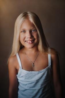 그녀의 아파트에서 아름 다운 금발 소녀의 초상화. 긴 느슨한 머리카락이 웃고 있습니다.