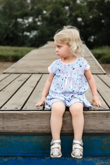 Портрет красивой белокурой девушки, сидящей на деревянном pantone. фото высокого качества