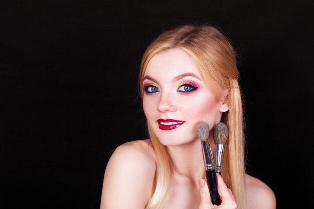 Портрет красивой блондинки с кисточками для макияжа в руках на черном