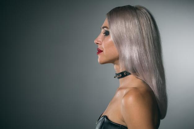 Портрет красивой блондинки с красными губами на темном фоне в воротнике с шипами