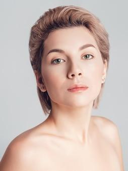 Портрет красивой блондинки с короткими волосами и зелеными глазами на сером фоне. макияж нюд, ретушь кожи