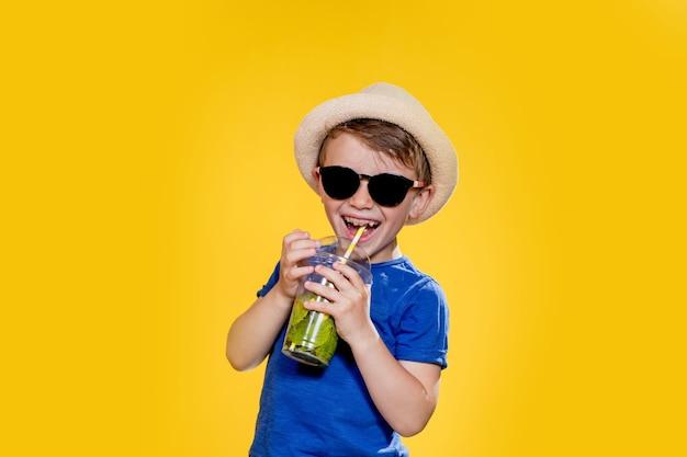 Портрет красивого мальчика. счастливый ребенок. европейский мальчик в шляпе, летней футболке с лимонадом. лето, отпуск, отпуск, солнце, жара, море, пляж. лицо для рекламы.