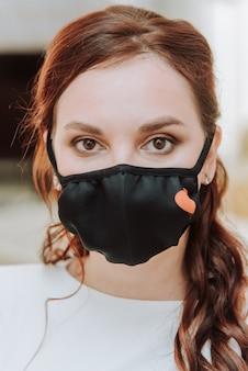 彼女の顔に医療用保護マスクを着用した美しい花嫁の肖像画。パンデミックコビッド-19の期間中の結婚式。