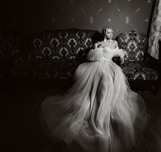 홀에 있는 아름다운 신부 초상화. 하얀 웨딩 드레스를 입은 우아한 신부가 의자에 앉아 있다. 흑백 사진