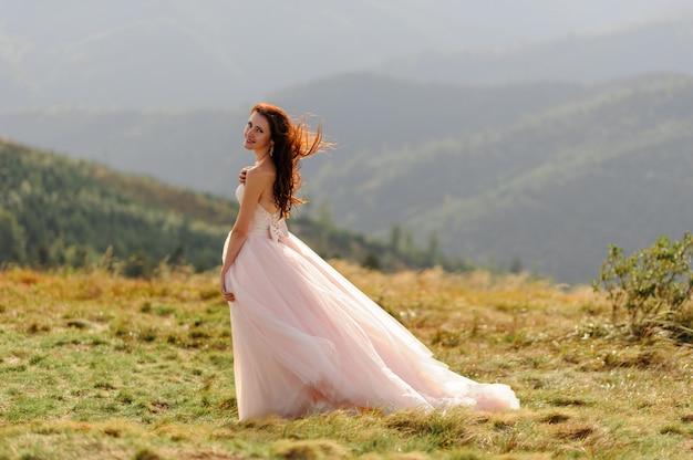 秋の山々を背景に美しい花嫁の肖像画。風が彼女の髪を吹きます。山の頂上での結婚式。フリースペース。