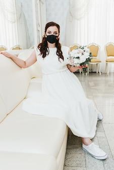 彼女の顔に医療用保護マスクの花束を持つ美しい花嫁の肖像画。パンデミックコビッド-19の期間中の結婚式。