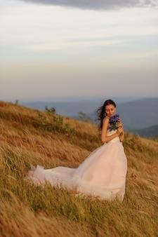 秋の山々を背景に野生の花「コーンフラワー」の花束を持つ美しい花嫁の肖像画。風が彼女の髪を吹きます。山の頂上での結婚式。フリースペース。