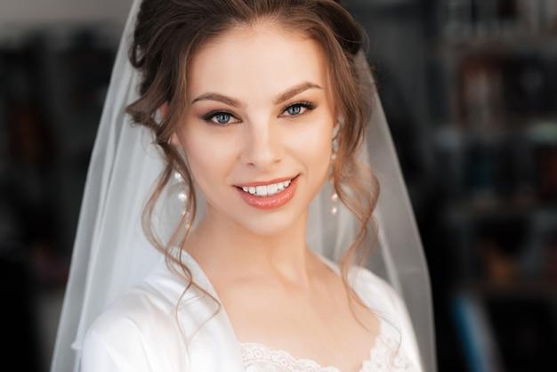 メイクや髪のスタイリングを笑顔で美しい花嫁の肖像画