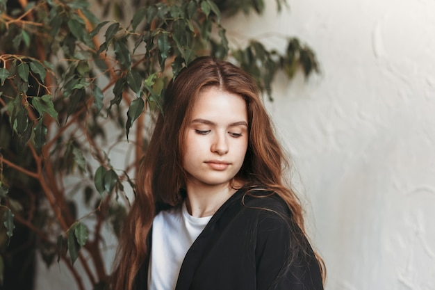 植物のあるアパートで長い髪の美しい陰気な少女の肖像画