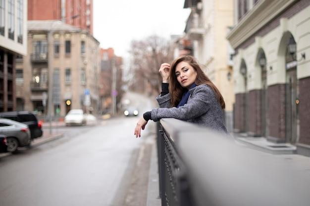 흐리게 도시 난간 근처 코트에 아름 다운 금발 여자의 초상화.