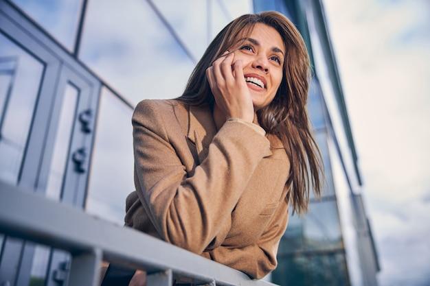 Портрет красивой брюнетки на фоне небоскребов в деловом районе